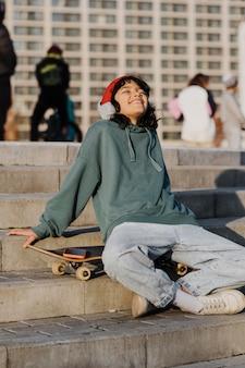 Nastolatek na zewnątrz słuchając muzyki na słuchawkach siedząc na deskorolce