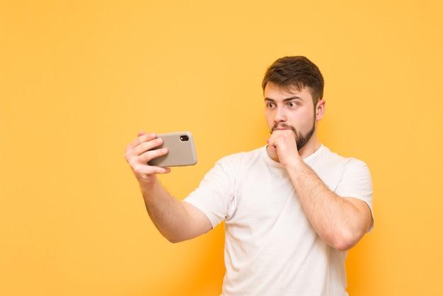 Nastolatek na żółto ze smartfonem w rękach, patrzy na ekran smartfona