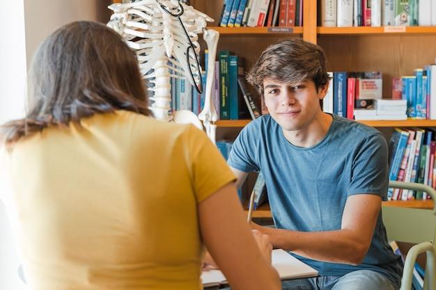 Nastolatek patrzeje kamerę podczas gdy studiujący z dziewczyną