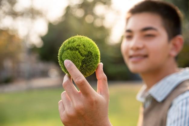 Nastolatek pokazuje ziemię pod ręką
