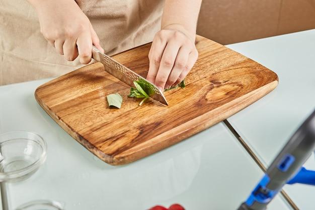 Nastolatek przygotowuje sałatkę z samouczka online i ogląda cyfrowy przepis na tablecie dotykowym, przygotowując zdrowy posiłek w domowej kuchni
