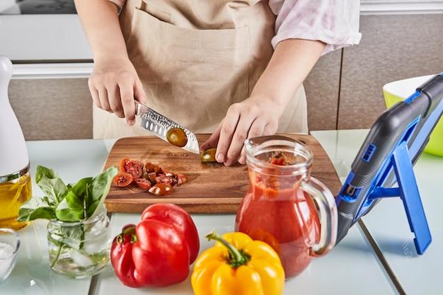 Nastolatek przygotowuje spaghetti bolognese z podręcznika online i ogląda cyfrowy przepis na tablecie z ekranem dotykowym, przygotowując zdrowy posiłek w domowej kuchni