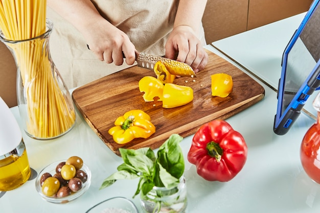 Nastolatek przygotowuje wirtualne seminarium online, kroi żółtą paprykę, przegląda cyfrowy przepis na tablecie z ekranem dotykowym, przygotowując zdrowy posiłek w domowej kuchni.