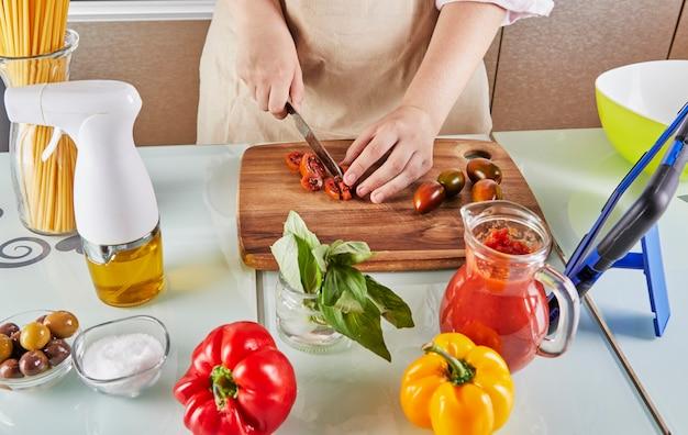 Nastolatek przygotowuje wirtualny samouczek online na podręczniku i ogląda cyfrowy przepis na tablecie z ekranem dotykowym, przygotowując zdrowy posiłek w domowej kuchni.