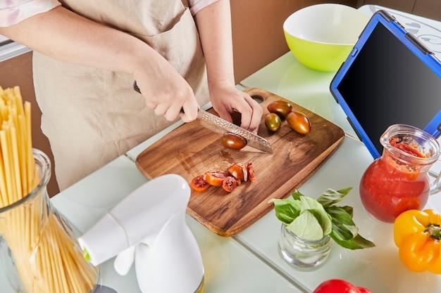 Nastolatek przygotowuje wirtualny samouczek online na podręczniku i ogląda cyfrowy przepis na tablecie z ekranem dotykowym, przygotowując zdrowy posiłek w domowej kuchni