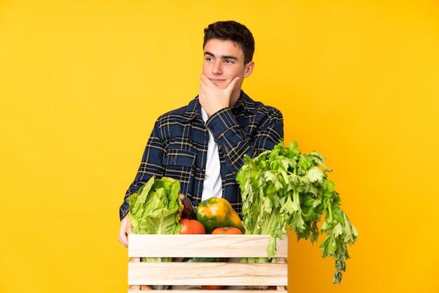 Nastolatek rolnik człowiek ze świeżo zebranych warzyw w pudełku myśląc pomysł