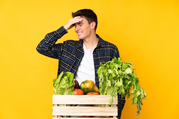 Nastolatek rolnik człowiek ze świeżo zebranych warzyw w pudełku