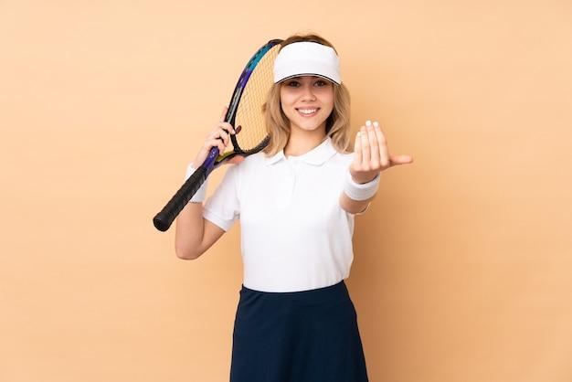 Nastolatek rosjanka na białym tle na beżowej ścianie, grać w tenisa i robi nadchodzący gest