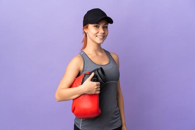 Nastolatek rosjanka na białym tle na fioletowej ścianie z rękawic bokserskich