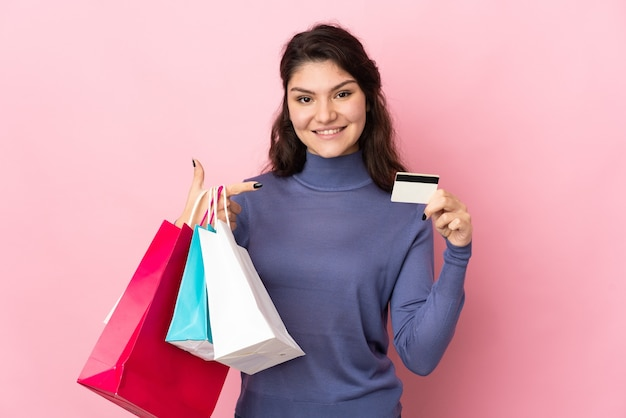 Nastolatek rosjanka na białym tle na różowym tle, trzymając torby na zakupy i kartę kredytową