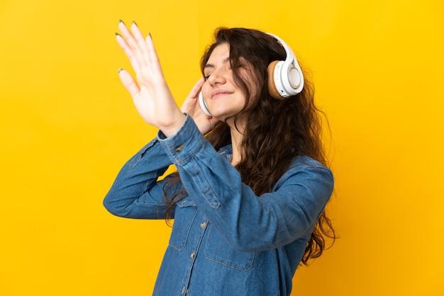 Nastolatek rosjanka na białym tle na żółtym tle słuchania muzyki i tańca