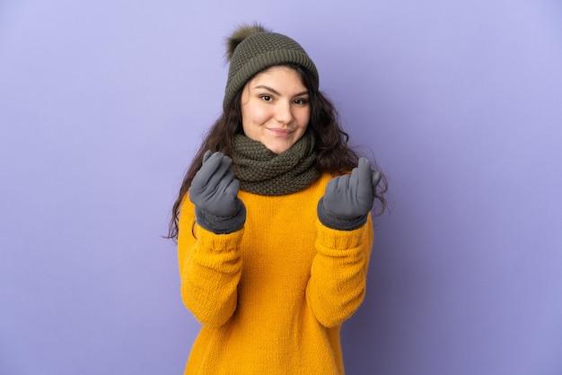 Nastolatek rosjanka z czapka zimowa na białym tle na fioletowej ścianie robi pieniądze gestowi