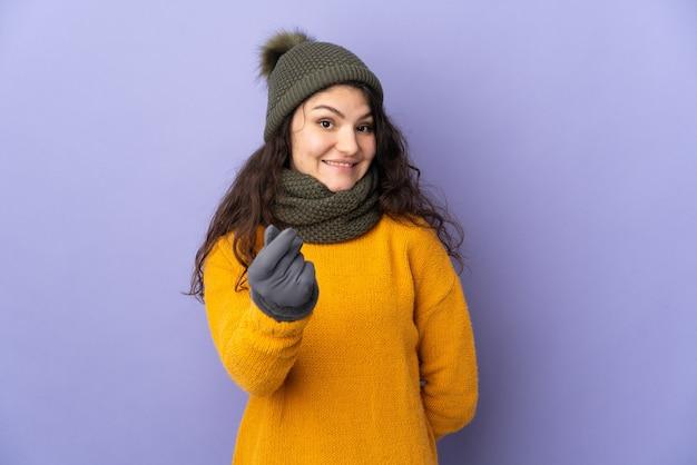 Nastolatek rosjanka z czapka zimowa na białym tle na fioletowym tle robi pieniądze gestowi