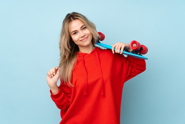 Nastolatek rosyjska kobieta odizolowywająca na błękit ścianie z łyżwą