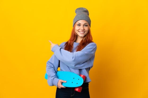 Nastolatek rosyjska łyżwiarka figurowa na białym tle na żółtej ścianie, wskazując z powrotem