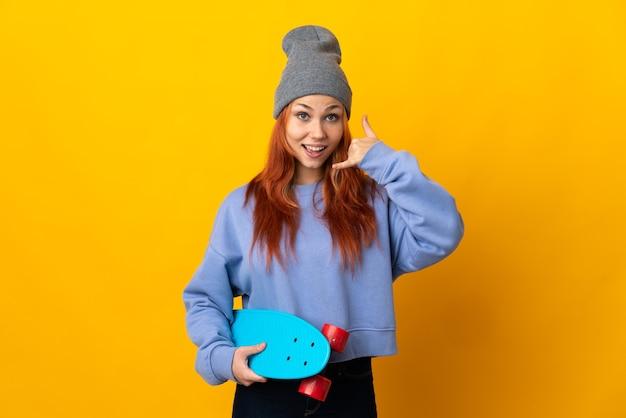 Nastolatek rosyjska łyżwiarz dziewczyna na białym tle na żółtej ścianie dzięki telefonowi gestowi. oddzwoń do mnie znak