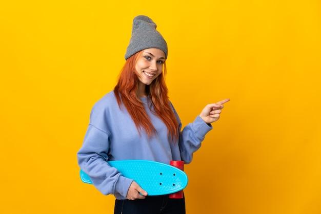 Nastolatek rosyjska łyżwiarz dziewczyna na białym tle na żółtej ścianie wskazując palcem na bok