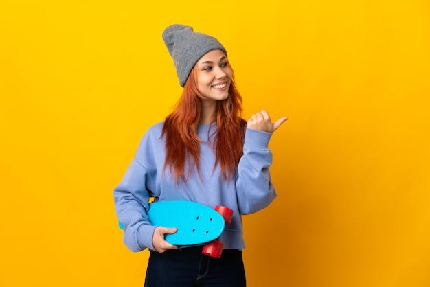 Nastolatek rosyjski skater dziewczyna na białym tle na żółtej ścianie, wskazując w bok, aby przedstawić produkt