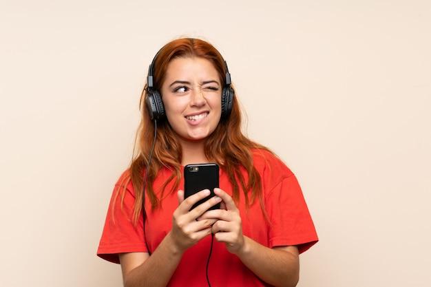 Nastolatek ruda dziewczyna słuchania muzyki za pomocą telefonu komórkowego i wątpliwości