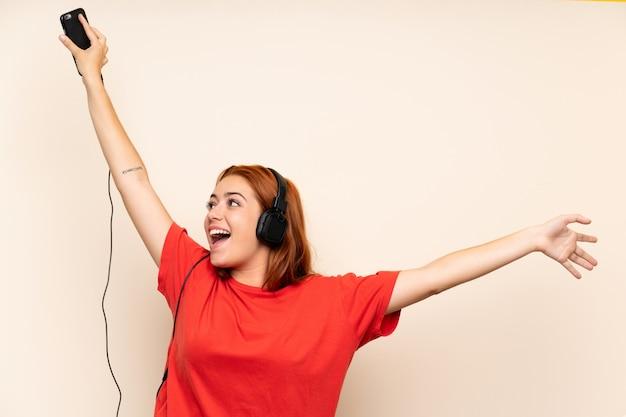 Nastolatek ruda dziewczyna słuchania muzyki za pomocą telefonu komórkowego