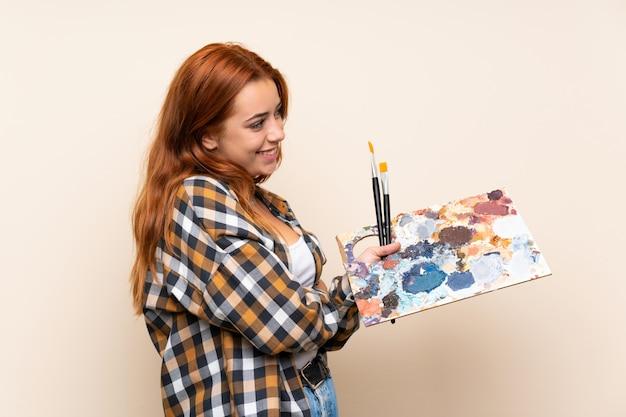 Nastolatek ruda dziewczyna trzyma paletę patrząc z boku