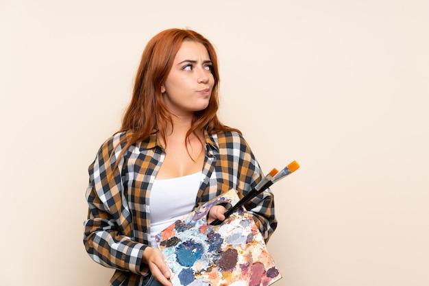 Nastolatek ruda dziewczyna trzyma paletę stojący i patrząc z boku