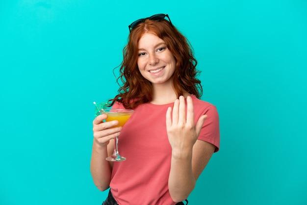 Nastolatek rude dziewczyny gospodarstwa koktajl na białym tle na niebieskim tle zapraszając przyjść z ręką. cieszę się, że przyszedłeś