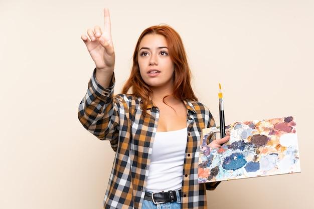 Nastolatek rude dziewczyny trzyma paletę na białym tle ściany dotykając przezroczystego ekranu