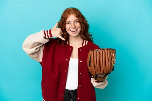 Nastolatek rude dziewczyny z rękawiczki baseballowej na białym tle na niebieskim tle co telefon gest. oddzwoń do mnie znak