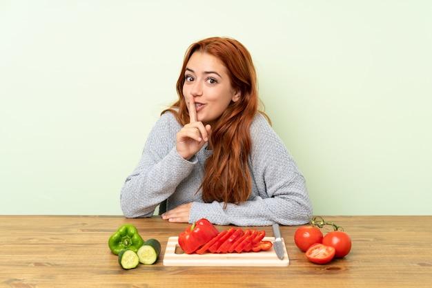 Nastolatek rude dziewczyny z warzywami w tabeli robi gest ciszy