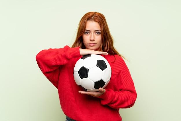 Nastolatek rudowłosa dziewczyna z sweter na pojedyncze zielone ściany gospodarstwa piłki nożnej