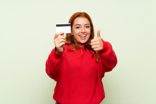 Nastolatek rudowłosa dziewczyna z swetrem na pojedyncze zielone gospodarstwa karty kredytowej