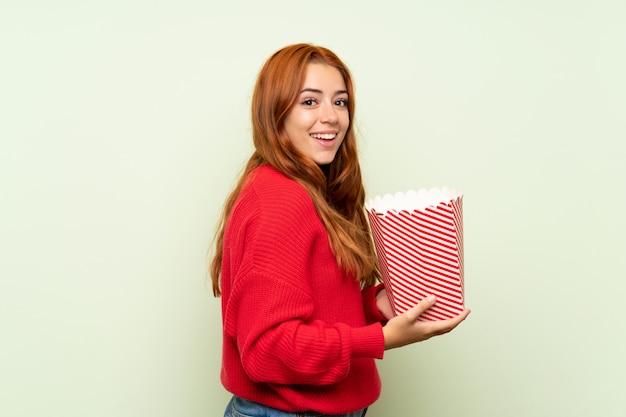 Nastolatek rudowłosa dziewczyna z swetrem na pojedyncze zielone gospodarstwa miskę popcorns