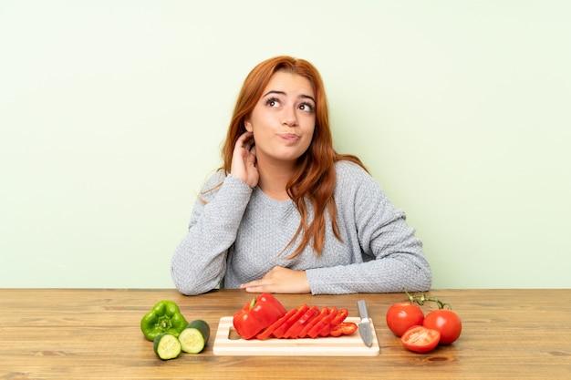 Nastolatek rudowłosa dziewczyna z warzywami w tabeli myślenia pomysł