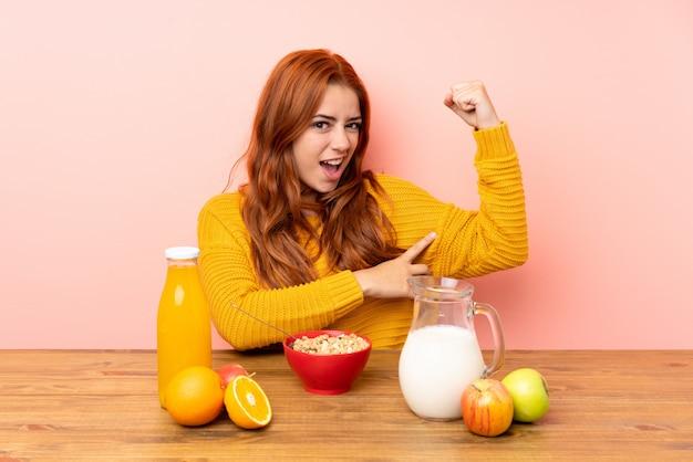 Nastolatek rudzielec dziewczyna ma śniadanie w stole robi silnemu gestowi
