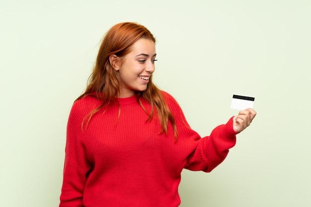 Nastolatek rudzielec dziewczyna trzyma kredytową kartę z pulowerem nad odosobnionym zielonym tłem