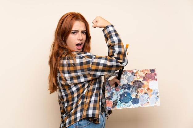 Nastolatek rudzielec dziewczyna trzyma paletę nad odosobnioną ścianą robi silnemu gestowi