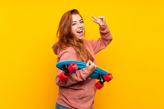 Nastolatek rudzielec dziewczyna z łyżwą nad odosobnioną kolor żółty ścianą
