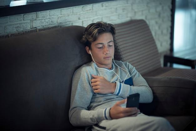 Nastolatek sam leżał na sofie w domu, używając telefonu i słuchając muzyki - oglądając filmy w nocy