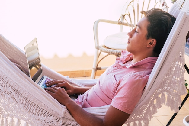 Nastolatek sam na tarasie w hamaku ogląda filmy, pracuje lub gra w gry wideo za pomocą telefonu lub komputera i telefonu - styl życia online i przyszłe pokolenia