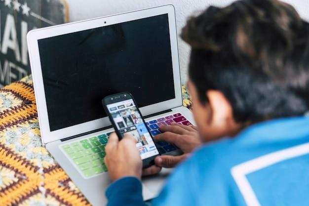 Nastolatek sam w sypialni na łóżku ogląda filmy, pracuje lub gra w gry wideo za pomocą laptopa lub komputera i telefonu - styl życia online i przyszłe pokolenia