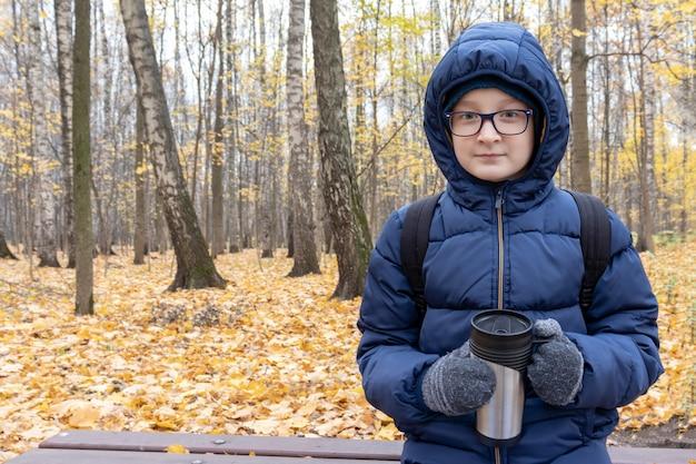Nastolatek siedzi na ławce w jesiennym parku z kubkiem termicznym wypełnionym gorącym napojem, kawą