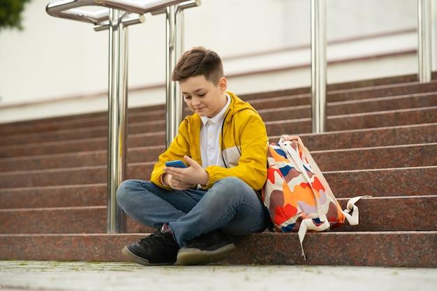 Nastolatek siedzi na schodach z telefonem