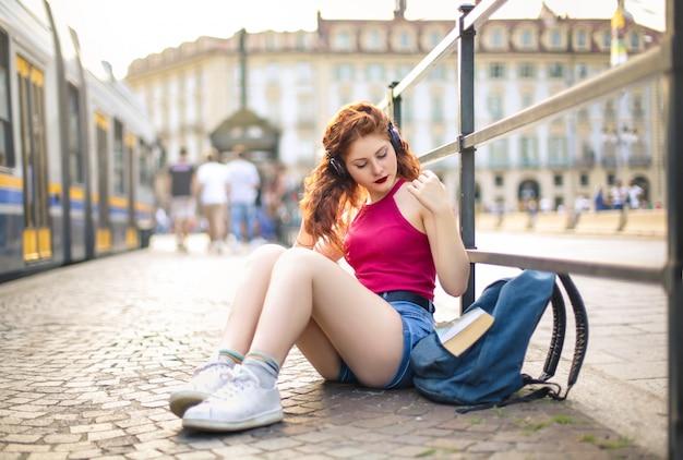 Nastolatek siedzi na ulicy słuchania muzyki