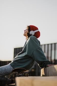 Nastolatek słucha muzyki na słuchawkach siedząc na deskorolce