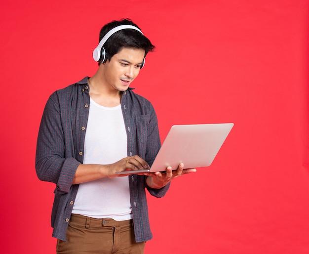 Nastolatek słucha muzyki przez słuchawki na notebooku