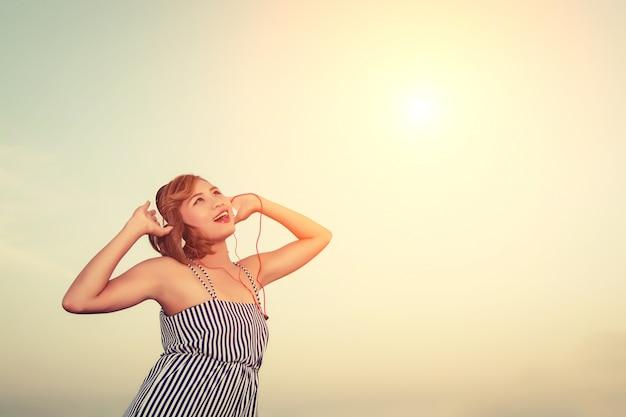 Nastolatek słuchanie muzyki w tle nieba
