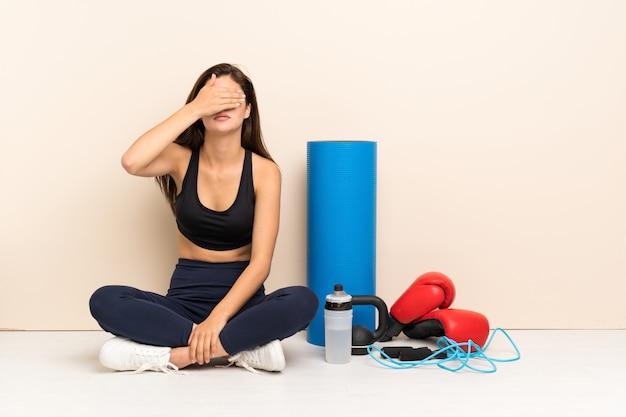 Nastolatek sporta dziewczyny obsiadanie na podłoga zakrywa oczy rękami. nie chcę czegoś widzieć