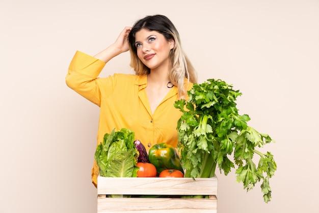 Nastolatek średniorolna dziewczyna ze świeżo zebranymi warzywami w pudełku odizolowywającym na beżowej ścianie ma wątpliwości i z zmieszanym wyrazem twarzy