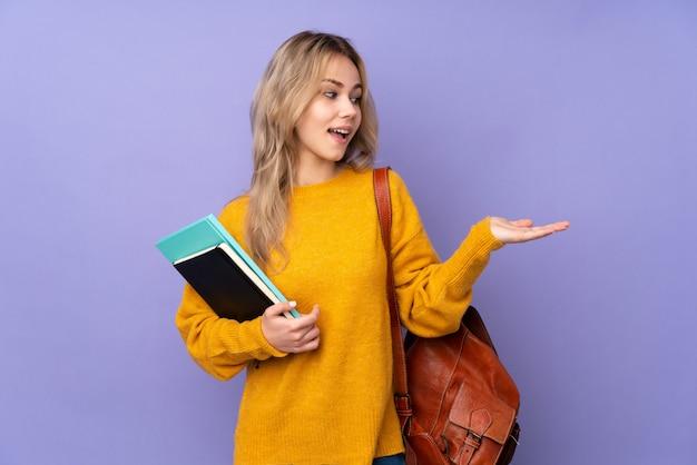 Nastolatek studencka dziewczyna na purpurowym mienia copyspace z dwa rękami